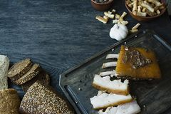 Baked pork belly with spices, fresh bread. Ukrainian fat. Traditional dish of Ukraine. Dark wooden background royalty free stock photos