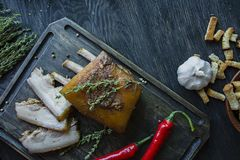 Baked pork belly with spices, thyme, bitter pepper, fresh bread. Ukrainian fat. Traditional dish of Ukraine. Dark wooden stock images