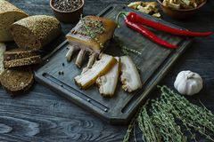 Baked pork belly with spices, thyme, bitter pepper, fresh bread. Ukrainian fat. Traditional dish of Ukraine. Dark wooden stock photos