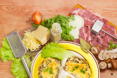 Baked pork chops with cheese and ingredients for their preparati Royalty Free Stock Photography