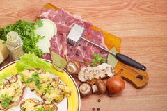 Baked pork chops with cheese and ingredients for their preparati Royalty Free Stock Image