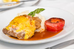 Baked Pork Cutlet. A breaded and baked pork cutlet with sauce and gravy, mashed potatoes, asparagus and broiled tomato stock photo