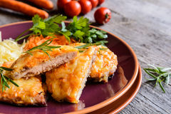 Baked pork cutlets coated in cheese and carrot with salad Stock Images