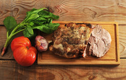 Baked pork ham with spices on a wooden Board Royalty Free Stock Photos