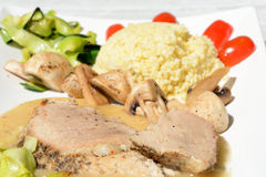 Baked pork loin, millet gruel, mushrooms and vegetables. Stock Images