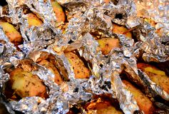 Baked pork meat in foil on baking tray Royalty Free Stock Images
