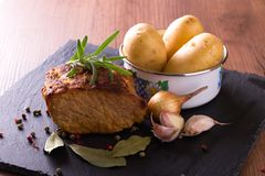 Baked pork meat with vegetable on slate stone. Horizontal photo of baked piece of pork meat with green rosemary herb on the top. Color pepper, bay leaf, onion Royalty Free Stock Photography