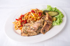 Baked pork meat with warm vegetable salad. Royalty Free Stock Photography