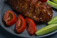 baked pork ribs with honey lie with fresh sliced tomatoes and cucumbers on a dark gray concrete tabletop stock images