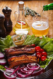 Baked pork ribs with vegetables and mustard and pouring beer from a bottle into a glass. On a wooden table Royalty Free Stock Photos