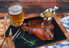 Baked pork shank, rosemary branch and honey sause and glass of b Royalty Free Stock Photography