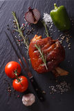 Baked pork shank, vegetables and spices on a slate. vertical top Royalty Free Stock Image