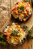 Baked portobello mushrooms stuffed with quinoa, vegetables and cheese with herbs on a  wooden board, vegetarian food Stock Photos