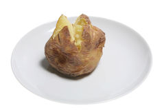 Baked Potato. Oven-baked potato on side plate, isolated on white Royalty Free Stock Photography