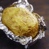 Baked potato in aluminium foil Stock Images
