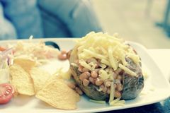 Baked Potato. A baked potato with beans and grated cheese - retro style Royalty Free Stock Photo