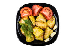 Baked potato in black glass plate with tomatoes and dill Royalty Free Stock Photo