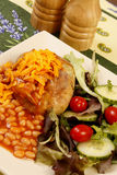 Baked potato cheese and beans. Baked potato with cheese, baked beans and a mixed leaf salad Stock Images