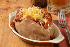 Baked potato with chili and cheese. A baked potato with chili and cheese and a mug of beer Stock Image