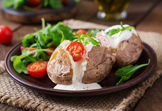 Baked potato. Filled with sour cream, arugula and tomatoes Royalty Free Stock Photography