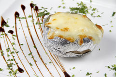 Baked potato in foil with cheese royalty free stock image