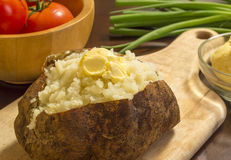 Baked potato. Fresh hot baked potato with butter on a cutting board stock images