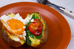 Baked potato with fried egg, feta, spinach and tomato cherry. Stock Photo