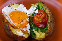 Baked potato with fried egg, feta, spinach and tomato cherry. Royalty Free Stock Image