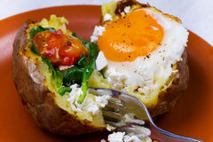 Baked potato with fried egg, feta, spinach and tomato cherry. Stock Photos