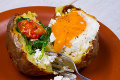 Baked potato with fried egg, feta, spinach and tomato cherry. Royalty Free Stock Images