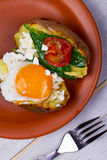 Baked potato with fried egg, feta, spinach and tomato cherry. Royalty Free Stock Photos