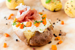 Baked potato and prosciutto Stock Photography