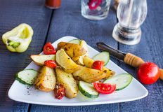 Baked potato and raw vegetables on a white plate. On the dark wooden board Stock Photos