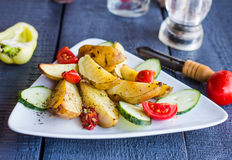 Baked potato and raw vegetables on a white plate, horizontally. Baked potato and raw vegetables on a white plate on the dark wooden board Stock Image