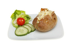 Baked potato and salad. Cheese topped baked potato with a salad garnish on a plate isolated against white stock images