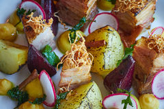 Baked potato slices and beets with vegetables and roast pork bacon close up Stock Image