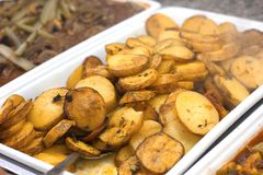 Baked potato slices on a white tray with a spoon stock photo