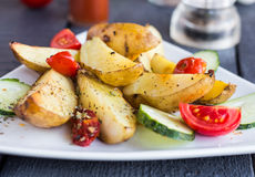 Baked potato, tomatoes and cucumbers on a white plate Stock Image