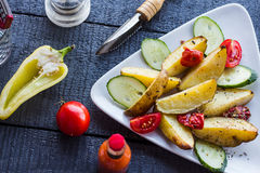 Baked potato, tomatoes and cucumbers  on a white plate Royalty Free Stock Photo