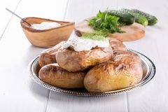 Baked potato topped with sour cream sauce royalty free stock image