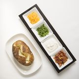 Baked potato with toppings. Royalty Free Stock Photos