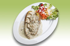 Baked potato with turkey ragout and mixed salad on plate Stock Image