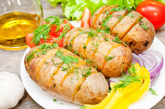 Baked potato with vegetables. Baked potato on a plate with vegetables stock photography