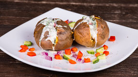 Baked potato with vegetables and sour cream Stock Images