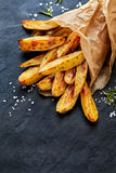 Baked potato wedges with addition  sea salt on a black background, top view Royalty Free Stock Images