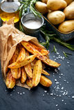 Baked potato wedges with addition  sea salt on a black background, top view Stock Photo