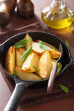 Baked potato wedges in black frying pan Stock Photography