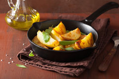 Baked potato wedges in black frying pan Stock Photos