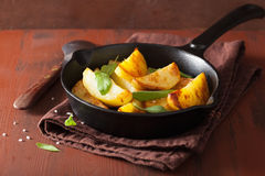 Baked potato wedges in black frying pan Stock Images