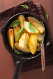Baked potato wedges in black frying pan Stock Photo